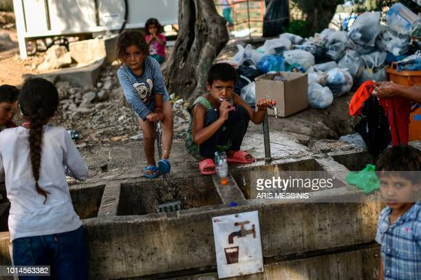 Refugees and migrants clean themselves and wash their clothes at a camp outside the Moria refugee camp in the island of Lesbos on August 5 2018