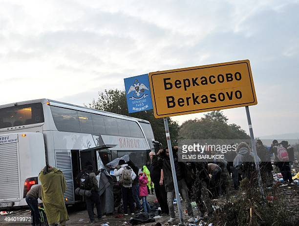 Refugees and migrants disembark from a bus at the SerbianCroatian border in the village of Berkasovo near the NorthWestern Serbian town of Sid on...