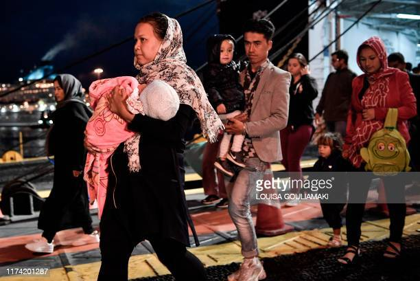 TOPSHOT Refugees and migrants disembark from a ferry upon their arrival from the island of Lesbos to the port of Piraeus near Athens early on October...