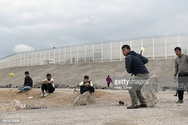Refugees and migrants from Afghanistan play cricket on a makeshift wicket which was once home to scores of refugees' tents to play cricket on May 10...
