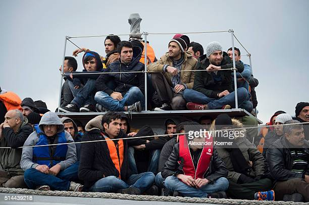 Refugees and migrants from Syria Afghanistan Nepal and Pakistan sit on deck of a vessel of the Greek Coast guard after trying to cross the sea from...