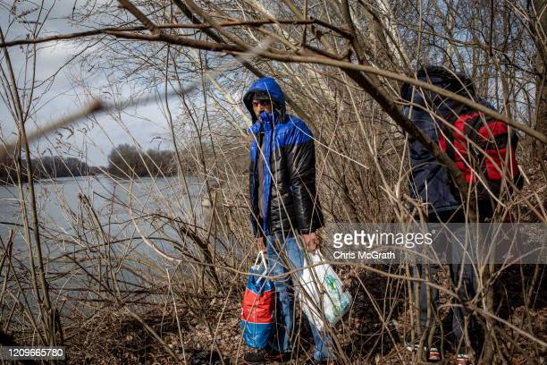 Refugees and migrants from various countries wait on the shoreline for a boat to cross the Evros River in an attempt to reach Greece from Turkey on...