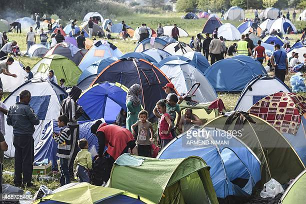 Refugees and migrants gather at a makeshift camp on the Serbian side of at the Hungarian border near the town of Horgos on September 17 the day after...