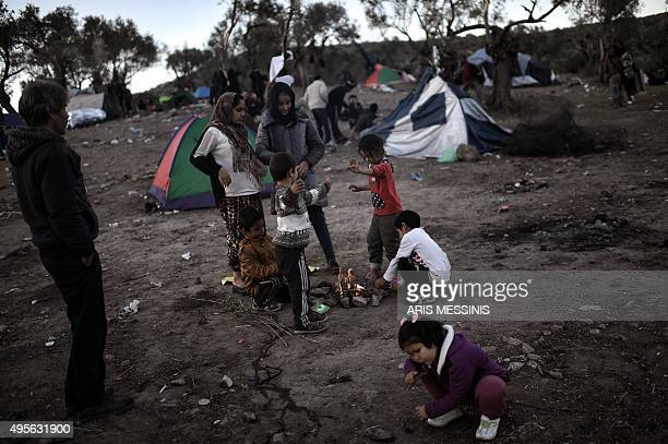 Refugees and migrants living in an olive grove next door to the Moria camp on the Greek island of Lesbos wait to register on November 4 2015 in...