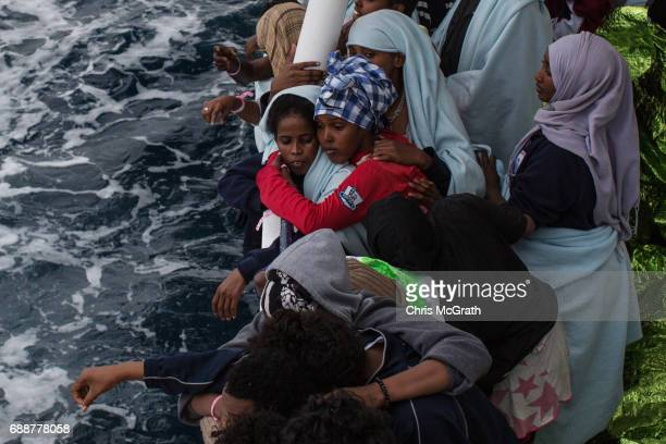 Refugees and migrants look out as they see the shoreline of Italy from on board the Migrant Offshore Aid Station 'Phoenix' vessel on May 26 2017 off...