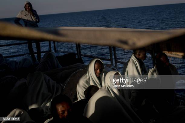Refugees and migrants look out at Italy as they arrive in port on the Migrant Offshore Aid Station Phoenix vessel on June 12, 2017 in Reggio...