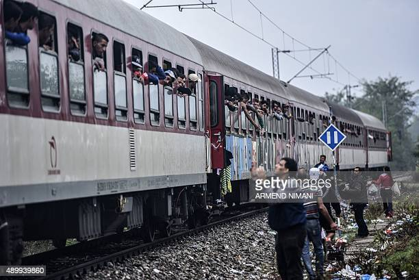 Refugees and migrants look out of windows aboard a train heading to Serbia near the MacedonianGreek border on September 25 2015 European Union...
