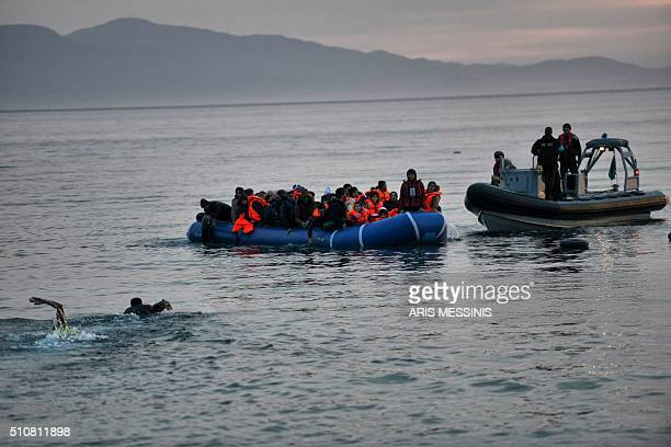 Refugees and migrants massed onto an inflatable boat reach Mytilene northern island of Lesbos after crossing the Aegean sea from Turkey on February...