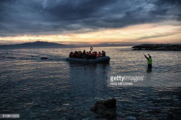 TOPSHOT Refugees and migrants massed onto an inflatable boat reach Mytilene northern island of Lesbos after crossing the Aegean sea from Turkey on...