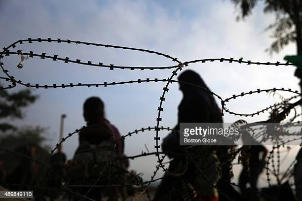 Refugees and migrants pass razor wire as they enter Macedonia at the border crossing outside of Idomeni Greece September 16 2015 From there the...