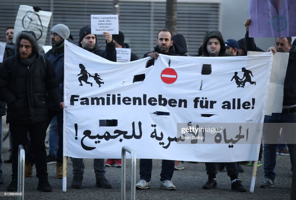 Refugees and migrants protest outside the Bundestag prior to debates and a vote over the rights of refugees who have been granted limited asylum in Germany to bring into Germany members of their immediate families on February 1, 2018 in Berlin, Germany. The German Christian Democrats (CDU/CSU) and the German Social Democrats (SPD), in their ongoing coalition negotiations, agreed yesterday on a compromise that starting August 1 the number of family members allowed to immigrate will be capped at 1,000 per month.