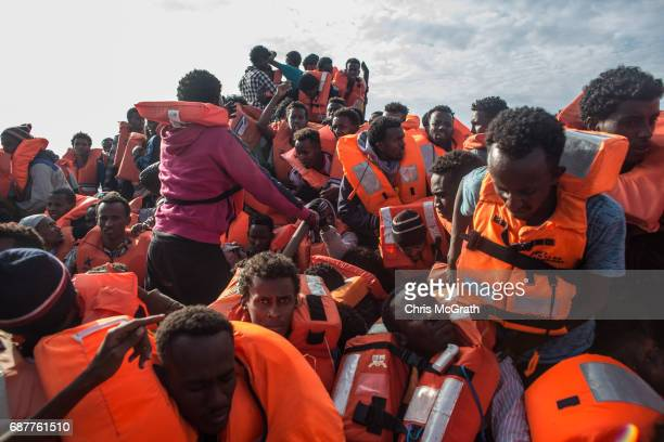 Refugees and migrants put on life jackets distributed by rescue crews of the Migrant Offshore Aid Station 'Phoenix' vessel on May 24 2017 off...