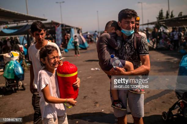 Refugees and migrants react after police threw tear gas during clashes near the city of Mytilene on the Greek island of Lesbos, on September 12 a few...