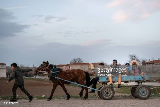 Refugees and migrants ride on a horse cart on a road towards the Pazarkule Border Crossing between Turkey and Greece on March 08, 2020 in Edirne,...