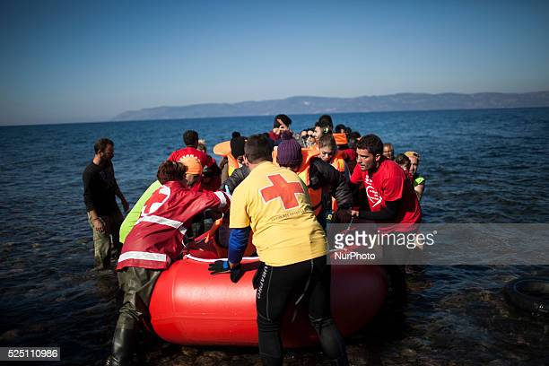 Refugees and migrants riding a dinghy reach the shores of the Greek island of Lesbos after crossing the Aegean Sea from Turkey on November 12 2015