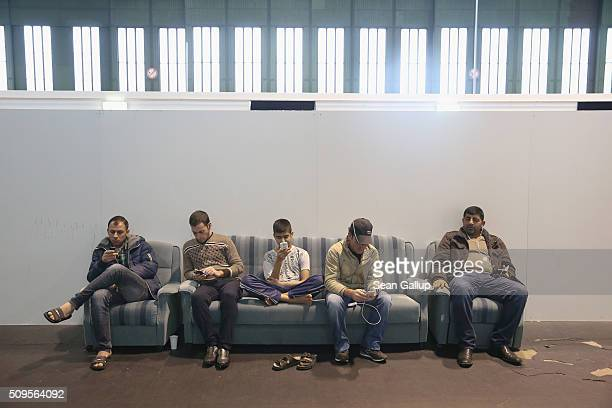 Refugees and migrants seeking asylum in Germany including men with smartphones sitting on a couch while away time in Hangar 7 where they live for now...