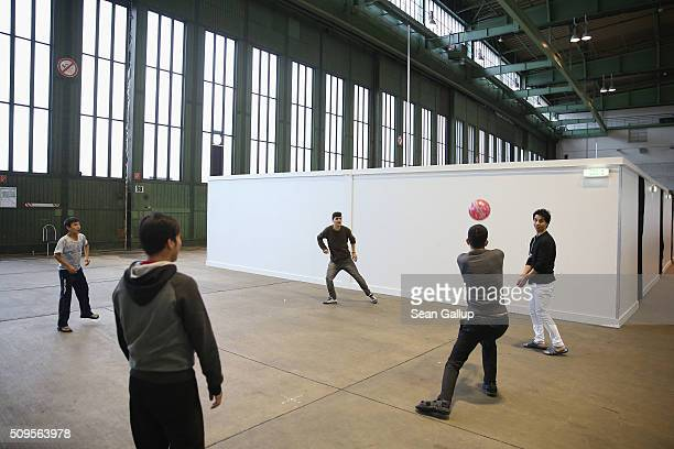 Refugees and migrants seeking asylum in Germany play volleyball in Hangar 7 at former Tempelhof Airport on February 11 2016 in Berlin Germany...