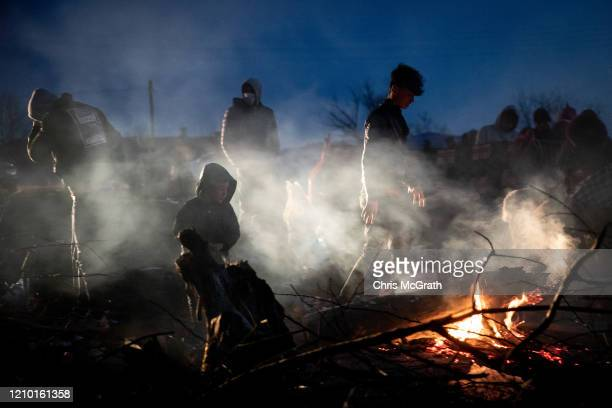 Refugees and migrants sit around a fire on the Turkish shoreline of the Evros River while they wait to cross by boat to Greece on March 03 2020 in...