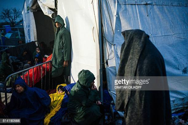 Refugees and migrants sit in the rain near the gate at the Greek-Macedonian border near the Greek village of Idomeni on March 7 where thousands of...