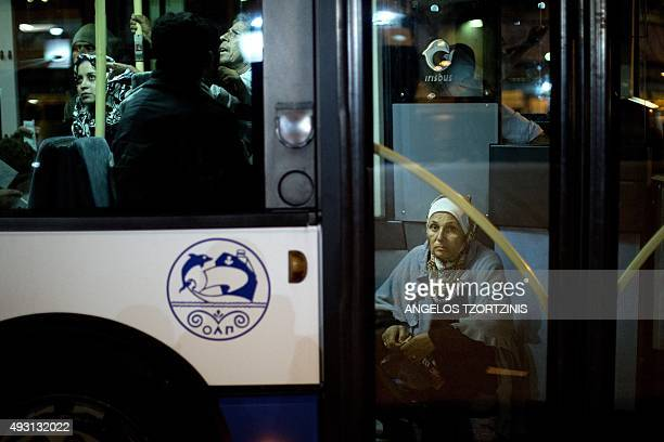 Refugees and migrants sit on a bus, shortly after disembarking from the 'Eleftherios Venizelos' ferry boat chartered by the Greek government, in the...