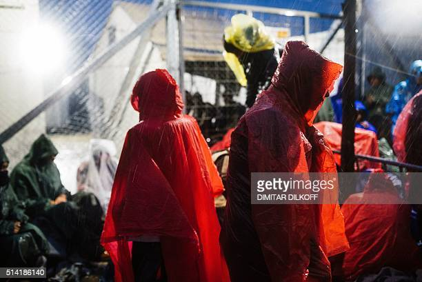 Refugees and migrants sit under the rain near the gate at the GreekMacedonian border near the Greek village of Idomeni on March 7 where thousands of...