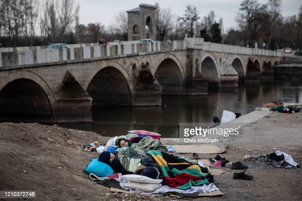 Refugees and migrants sleep next to the Edirne Old Bridge on March 04 2020 in Edirne Turkey Thousands of refugees and migrants have flocked to the...