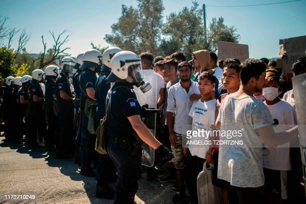 Refugees and migrants stand in front a riot police during in a demonstration against their living conditions at the Moria camp on the island of...