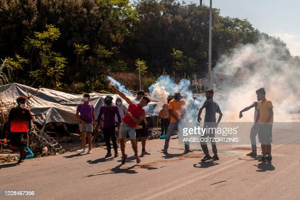 Refugees and migrants throw back tear gas canisters fired by riot police during clashes near the city of Mytilene on the Greek island of Lesbos, on...