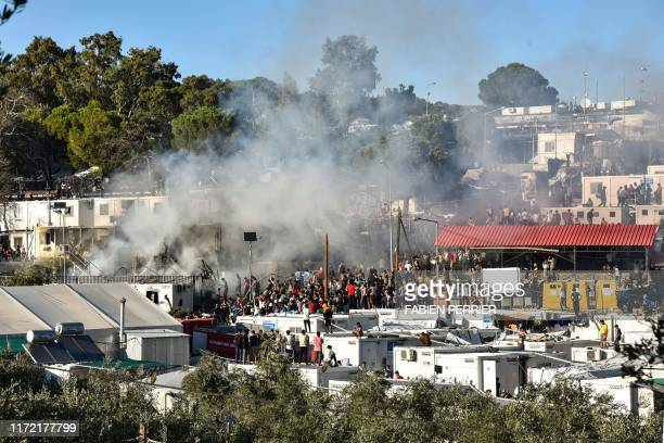 Refugees and migrants try to escape the camp of Moria after a fire broke out in the camp in Mytilene on September 29 2019