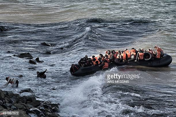 Refugees and migrants try to reach the shore on the Greek island of Lesbos despite a rough sea on October 30 after crossing the Aegean sea from...