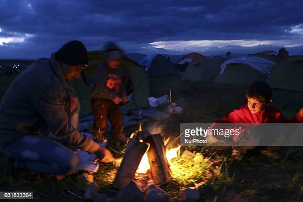 Refugees and migrants try to warm themselves through fires in the makeshift camp in Idomeni, Greece February 2016. They use everything to sustain the...