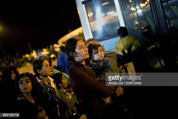 Refugees and migrants wait for buses after disembarking from the 'Eleftherios Venizelos' ferry boat chartered by the Greek government in the port of...
