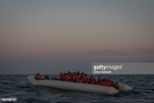 Refugees and migrants wait in a small rubber boat to be rescued by crewmembers from the Migrant Offshore Aid Station Phoenix vessel on June 10 2017...