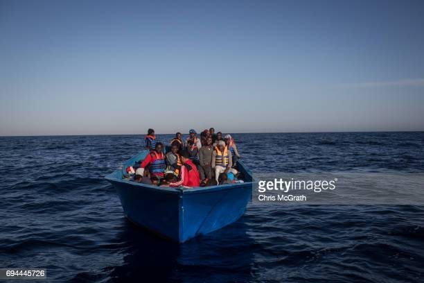 Refugees and migrants wait in a small wooden boat to be rescued by crewmembers from the Migrant Offshore Aid Station Phoenix vessel on June 10 2017...