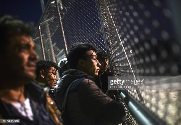 Refugees and migrants wait in front of a gate for registration in a camp on the Greek island of Lesbos after crossing the Aegean Sea from Turkey on...