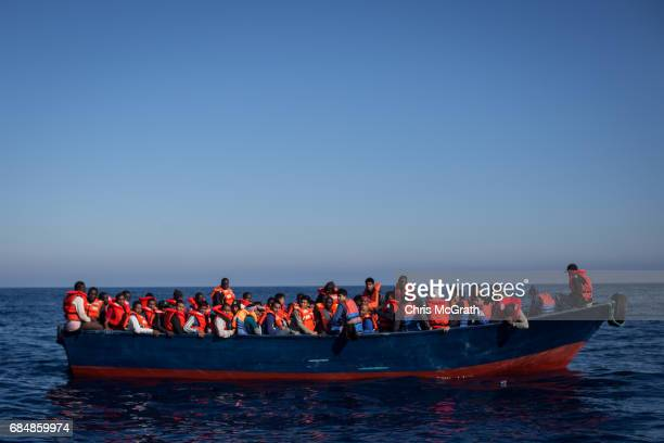 Refugees and migrants wait to be rescued from an overcrowded boat by crew members from the Migrant Offshore Aid Station Phoenix vessel on May 18 2017...