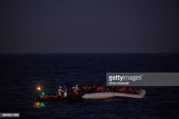Refugees and migrants wait to be rescued in the early housr of the morning by crewmembers from the Migrant Offshore Aid Station Phoenix vessel on...