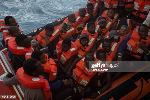 Refugees and migrants wait to be transfered onboard the Migrant Offshore Aid Station Phoenix vessel after being rescued at sea earlier in the day on...