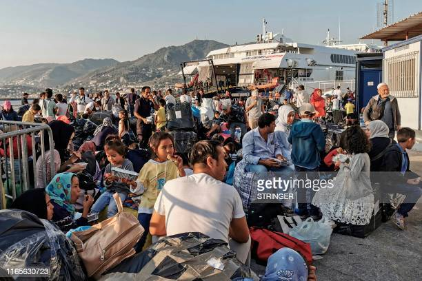 Refugees and migrants wait to board on a ship at the port of Mytilene in the island of Lesbos on September 2 2019 Hundreds of migrants leave Lesbos...
