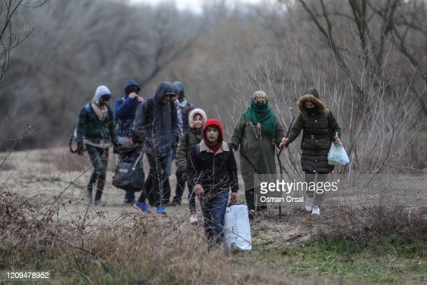 Refugees and migrants walk as they attempt to enter Greece from Turkey by crossing the Evros river on February 29, 2020 in Edirne, Turkey. Turkey...