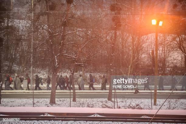TOPSHOT Refugees and migrants walk to cross the SlovenianAustrian border on January 5 2016 in Sentilj / AFP / Rene Gomolj