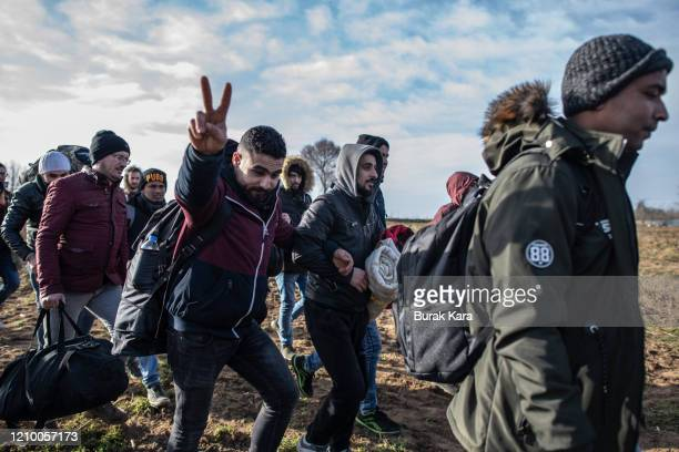 Refugees and migrants walk with their belongings to the Turkey's Pazarkule border crossing with Greece's Kastanies on March 03, 2020 in Edirne,...