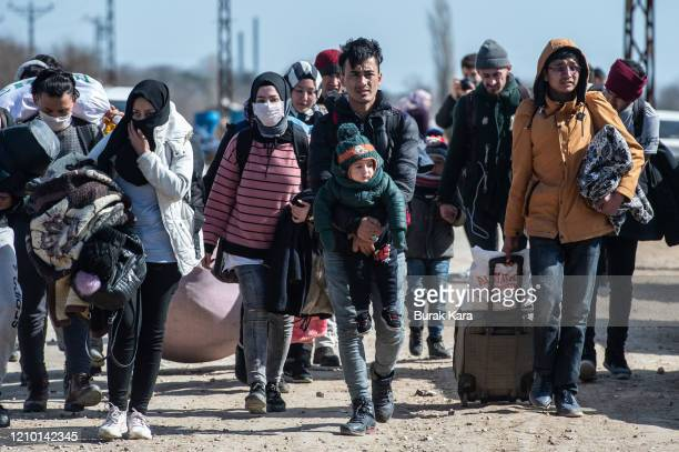 Refugees and migrants walk with their belongings to Turkey's Pazarkule border crossing with Greece's Kastanies on March 03 2020 in Edirne Turkey...