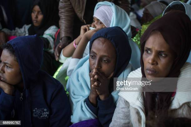 Refugees and migrants watch on as they wait to disembark the Migrant Offshore Aid Station 'Phoenix' vessel on May 27 2017 in Crotone Italy The...