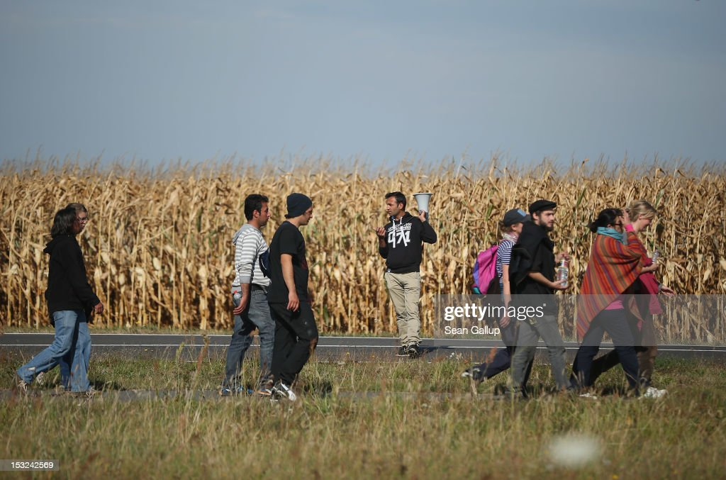 Refugees and supporters walk past a field of corn along a country road during their protest march across nearly 600km from Wuerzburg to Berlin on October 2, 2012 near Bad Belzig, Germany. Approximately 25 refugees from Iran, Iraq, Afghanistan, Turkey and other nations who are seeking political asylum are marching to protest the conditions under which they live in Germany. Asylum seekers in Germany are by law prohibited from working and their ability to travel is very restricted. The group expects to arrive in Berlin on October 6.
