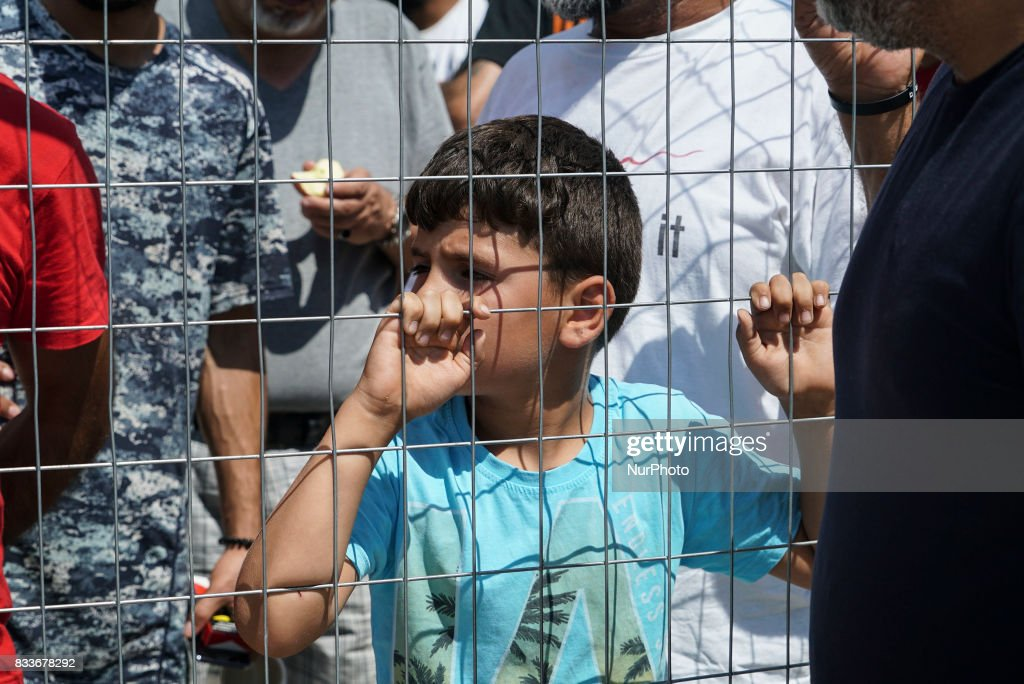 Refugees are protesting in Diavata Camp (Former Anagnostopoulou military camp), in Thessaloniki, Greece, on August 17, 2017. They blocked the entrance and rushed out all the government and ngo employees including army and police. Refugees and migrants are from Syria, Iran, Afghanistan, Pakistan and Kurdish in this camp. They are protesting because in the transformed house containers that they live, more people will come. The camp hosts about 350 people with AC, kitchen, WC in each container and the number of the guests can be expanded at least for more 20%. The government is bringing , actually relocation from camps in bad conditions from the islands, 27 people by bus to this camp. Each container house can host 6 people. For the moment in most of the houses live 4 people. Refugees even denied to reunite their families that hold two containers. The ministry arranged a few empty containers but refugees and migrants still keep protesting. Other demands from the refugees are to leave the camp and live in house, relocate to European countries like Germany and organize a school in the camp for little children. Local authorities and police are blocked outside of the camp. The temperature in the camp is about 36°C right now and they still stay outside.