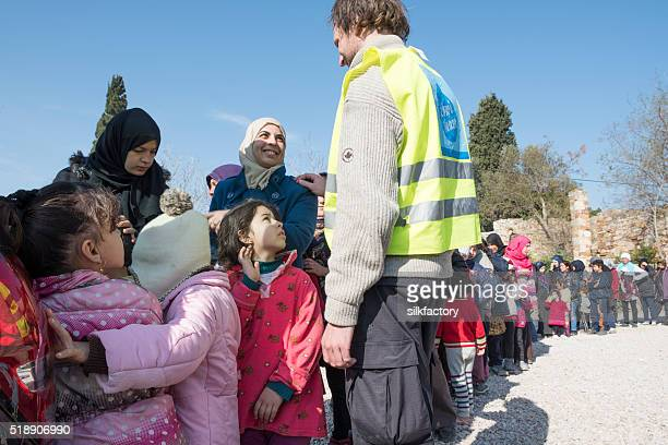 Refugees are standing in line to be served breakfast