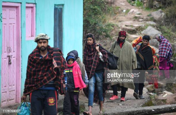Refugees arrive at a community relief camp carrying personal belongings after hundreds flee their home at Chhajla village in India's Mendhar near the...