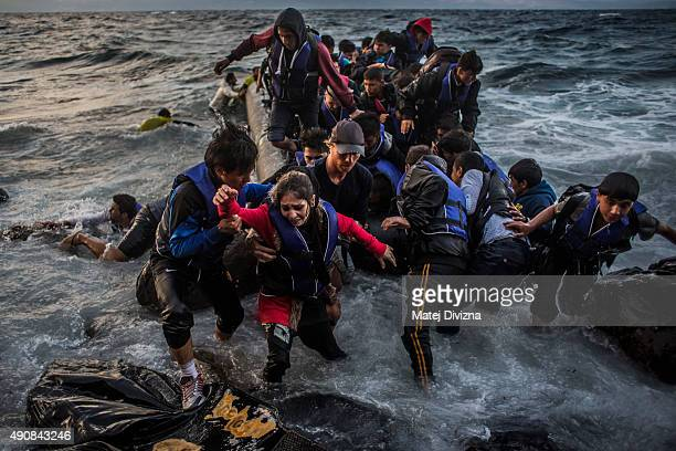 Refugees arrive on the shores of the Greek island of Lesbos after crossing the Aegean sea from Turkey on an inflatable boat on October 1 2015 near...