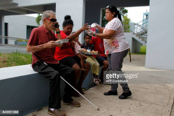 Refugees at a hurricane shelter get breakfast as Hurricane Irma approaches Puerto Rico in Luquillo on September 6 2017 Irma is expected to reach the...